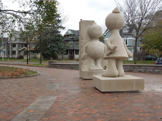 """In Tom Otterness' """"Creation Myth,"""" a female sculptor tries to carve a male from a block of stone. The original female figure seen here was made from limestone and has been replaced with a bronze version."""