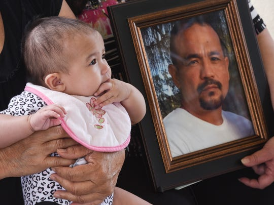 Four-month-old Gaidalynn Joy Alvarez, sits on the lap of her grandmother, Christina Pangelinan Alvarez, as she is photographed alongside an image of her father, Gilbert Alvarez Jr., at the Paseo in Hagåtña on Tuesday, March 7, 2017.