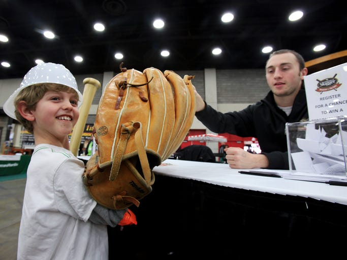 "Jude Jamison, 8, left, tries on the ""'Big Baseball Mitt"" as Michael Dean, of the Louisville Slugger Museum, steadies it for him during the Home, Garden and Remodeling Show in the south wing of the Kentucky Exposition Center. Mar. 2, 2014"