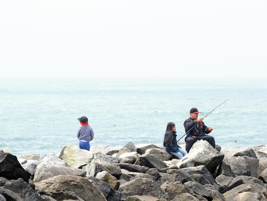 Anglers working the rocky breakwater near Moss Landing