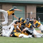 Hartland players pile up on Brett Oliver as they celebrate winning the school's first baseball state championship on Saturday. R.J. Bortle, who scored the winning run, is airborne at left.