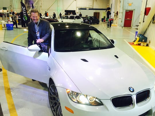 Fred Cartwright, executive director of Clemson University's International Center for Automotive Research, hops into a BMW Wednesday for a ride on a test track at the International Transportation Innovation Center.