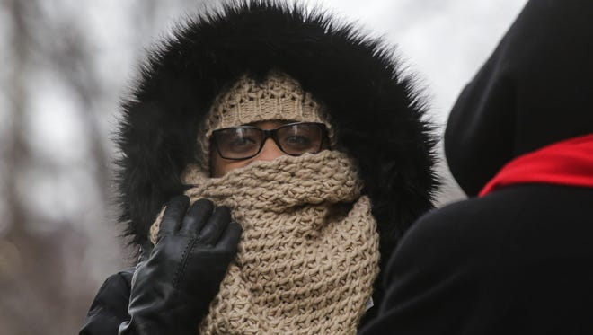 Valerie Coleman of Detroit covers her face while waiting for a bus on Woodward near Congress in downtown Detroit last week. Frigid temperature return Thursday, but a warm-up is in store for the weekend.