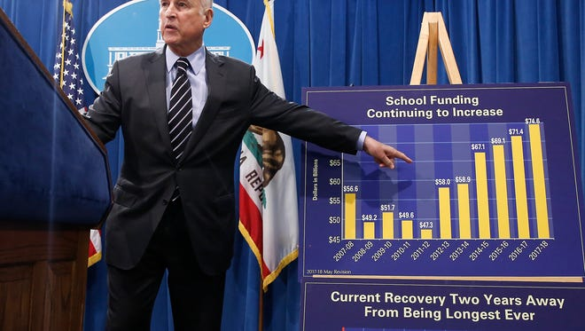 California Gov. Jerry Brown gestures to a chart showing the increase spending for school funding while discussing his revised $124 billion state budget plan in May in Sacramento.