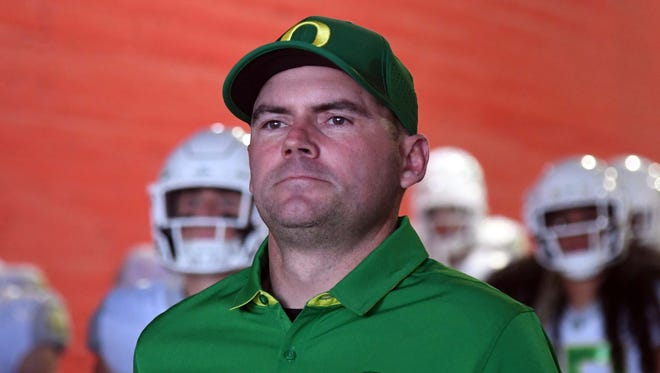 Helfrich enters the field before a game against USC in Los Angeles.