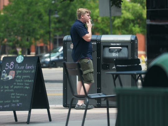 A man smokes on the corner of North College Avenue