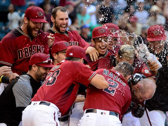 Arizona Diamondbacks left fielder Chris Herrmann celebrates with teammates after hitting a walk off home run in the eleventh inning against the Mets at Chase Field.