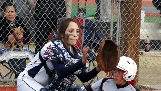 Lady Cat catcher Valerie Lopez focuses on the softball coming home behind the Centennial runner during first-game action Tuesday at E.J. Hooten Park. Lopez and the Lady Wildcats varsity softball team were swept by the Hawks in double-header action, 16-7 and 18-1.