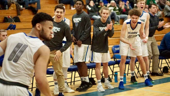 Olympic senior Jaiden Mosley earns cheers from his teammates after a layup against Port Angeles on Thursday. The Trojans won 76-58 to take second place in the Olympic League 2A.