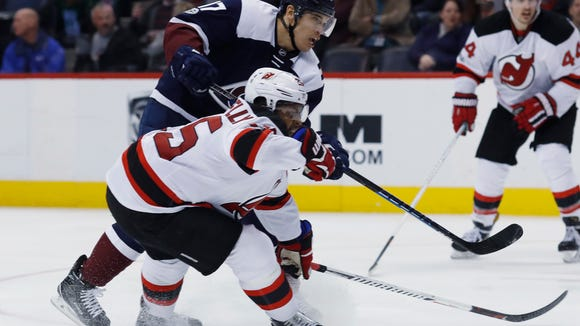 Colorado Avalanche right wing Rene Bourque, back, fires the puck past New Jersey Devils right wing Devante Smith-Pelly for a goal during the third period of an NHL hockey game Thursday, March 9, 2017, in Denver. The Avalanche won 3-2. (AP Photo/David Zalubowski)