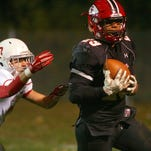 Coshocton junior Kobie Means completes a pass for a touchdown Friday during the team's 35-21 loss to Dover.