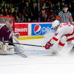 Cornell senior captain John McCarron tries to slip the puck past Colgate goalie Charlie Finn during the second period of Saturday night's game against Colgate at sold-out Lynah Rink. McCarron scored his first goal of the season in the third to help the Red tied the Raiders, 2-2.