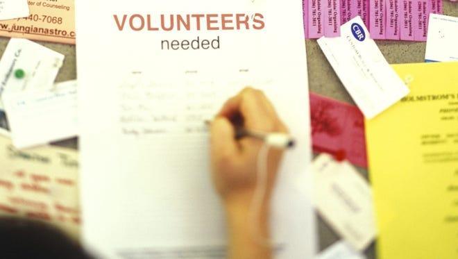Person signing 'Volunteers needed' flier.