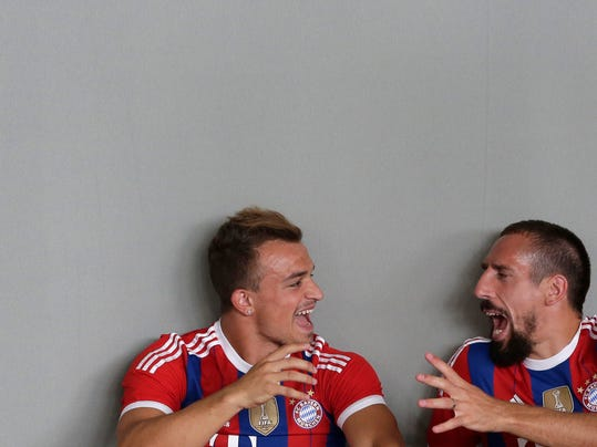 Bayern Munich's Xherdan Shaqiri, left, and Franck Ribery joke during an official photo shooting for the new German first division Bundesliga season in Munich, southern Germany, Saturday, Aug. 9, 2014. (AP Photo/Matthias Schrader)