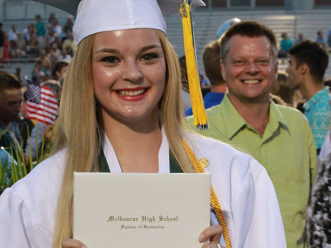 Ashleigh Oleander proudly displays her diploma as her father proudly looks on after the Melbourne High School 2014 graduation.