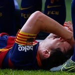 FC Barcelona's Lionel Messi lies on the pitch injured