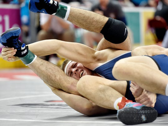 Chambersburg's Drew Peck, front, is all tangled up with Bayard Rustin's Csts Hatzipavlides in a 182-pound quarterfinal bout in the PIAA Class AAA tournament Friday at Giant Center. Peck won 9-5.