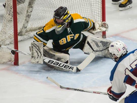 The BFA St. Albans goalie Daniel Ellis deflects a shot from Spaulding's #17 Luke Krupa during the D1 boys hockey Vermont State Championship Thursday night at UVM. BFA won 2-1.