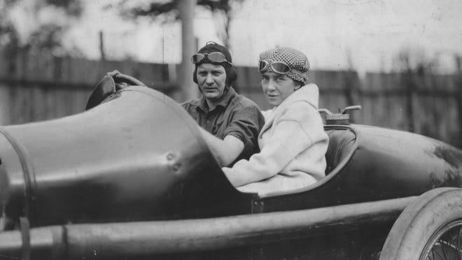 Mary Bostwick, seen here with Howdy Wilcox, was the first woman to ride in a race car on the Indy Motor Speedway at racing speed (110 mph).