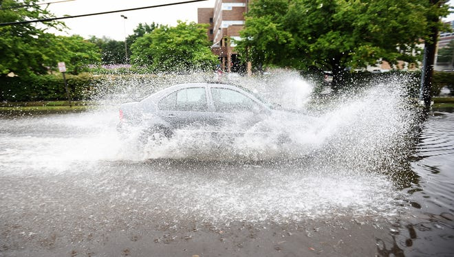 Flooding on South Newman Street in Hackensack, NJ on Friday August 18, 2017. A car drives through the water.