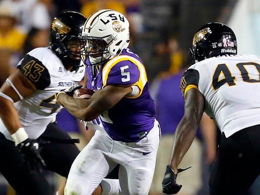 FILE - In this Oct. 15, 2016, file photo, LSU running back Derrius Guice (5) cuts between Southern Mississippi defensive lineman LaDarius Harris (43) and linebacker C.J. Perry (40) during the second half of an NCAA college football game in Baton Rouge, La. Guice, a junior who emerged as LSU's leading rusher last season, enters the 2017 campaign as the most accomplished and dynamic player in a new offense installed by first-year coordinator Matt Canada.  (AP Photo/Butch Dill, File)