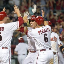 Arizona Diamondbacks infielder Jake Lamb celebrates with teammates at home plate after hitting a grand slam in the 8th inning of their baseball game against the Colorado Rockies in the sixth inning at Chase Field in Phoenix on Friday, August 29, 2014.
