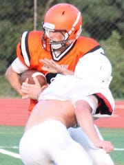 Anderson quarterback Dylan Smith eludes a tackle during