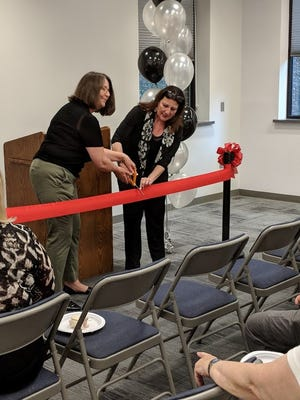 Sayreville Public Library Board of Trustees President Anne Pulnik and the Library Director Leah Kloc cut the ribbon to officially mark the opening of the renovated meeting room.