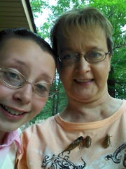 Jennifer Brazzell (right) lets periodical cicadas crawl on her shirt outside her home in Georgetown. Her 11-year-old daughter, Arianna (left), won't touch the creatures, which have emerged by the millions in Central Louisiana after going underground for 13 years.