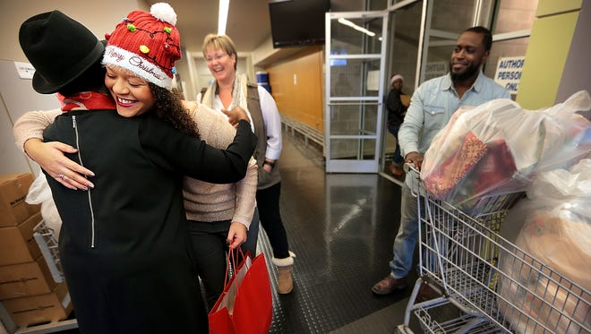 MIFA volunteer Victoria Vicks hugs members of the MIFA staff as she and her foster mother Tammera Freno pick up meals for delivery. MIFA volunteers delivered over 800 Christmas meals this year.