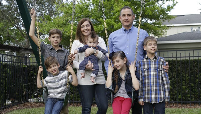 Francisco and Lauren Nieves-Taranto, center, with their children, from left, Sebastien, 13, Javier, 6, Nicolas 4-months, Valentina, 8, and Gabriel, 10, at their home in Windermere, Fla. Nieves-Taranto covered the entire $8,000 bill from the birth of Nicolas last year with his account balance from a health savings account, or HSA.