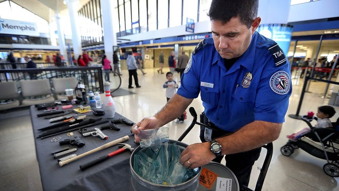 TSA Lead Officer William Brechin pulls ammunition out of a bucket that was confiscated recently along with an example of the guns, knives, tazers, and other items that could be used as weapons surrendered by travelers passing through Memphis security. TSA officials assembled the display as part of a press gathering to talk about travel safety Tuesday morning at Memphis International Airport.