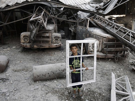 A Palestinian youth holds a window frame as he inspects a destroyed building in the Al-Shejaea neighbourhood of Gaza City  after a 72-hour truce agreed by Israel and Hamas went into effect following intense global pressure to end the bloody conflict.