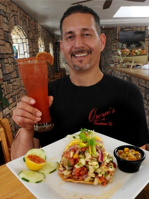 Guillermo Orozco, owner of Orozco's on Front Street in Ventura, displays the Tostada de ceviche with a Michelada.