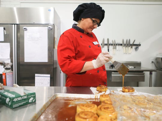 Employee Shaunta Jones drizzles more icing on a cinnamon