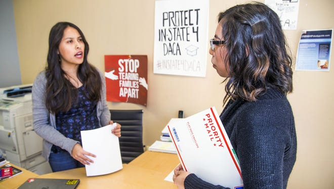 19-year-old Abigail Gayosso, right, of Phoenix, holds on to her Deferred Action for Childhood Arrivals renewal application while asking program coordinator Vianey Perez a question Jan. 24, 2018, at the Arizona Dream Act Coalition in Phoenix.