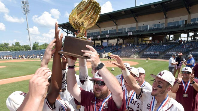 The Nanih Waiya Warriors and head Tyler Rogers celebrate with the Class 1A trophy after beating Smithville in game two of the series on Friday, May 18, 2018, in the MHSAA State Baseball Championships at Trustmark Park in Pearl, Miss.
