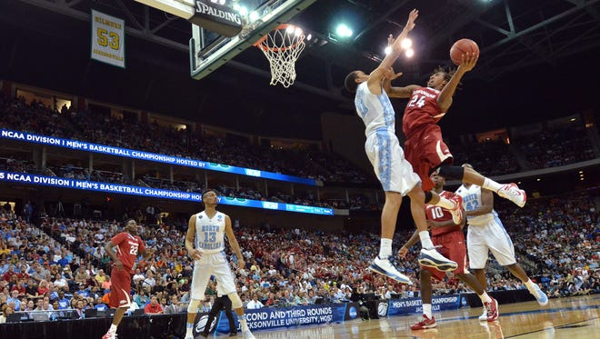 Arkansas guard Michael Qualls (24) shoots in front of North Carolina forward Brice Johnson (11) during the first half of an NCAA tournament third round basketball game Saturday, March 21, 2015, in Jacksonville, Fla.  (AP Photo/Rick Wilson)