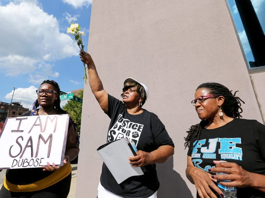Audrey DuBose (center), mother of Samuel DuBose, reacts to the Black Lives Matter rally moving down Central Parkway. With her are Shannae Figgs (left) and Shannon DuBose, both cousins of Samuel DuBose.