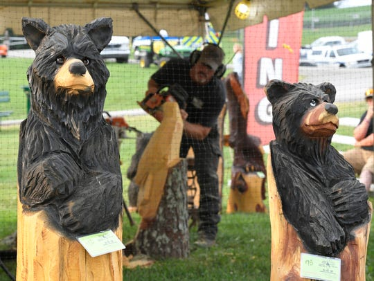 Chainsaw artist Roark Phillips carves behind two of