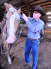Co-owner Jeff Chism readies his mount for a ride at Chism Trail Ranch in Merrill.