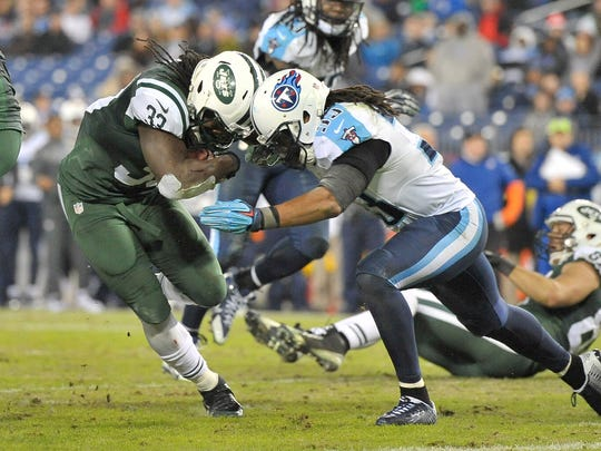 Dec 14, 2014; Nashville, TN, USA; New York Jets running back Chris Ivory (33) rushes against Tennessee Titans free safety Michael Griffin (33) during the second half at LP Field. Jets won 16-11. Mandatory Credit: Jim Brown-USA TODAY Sports