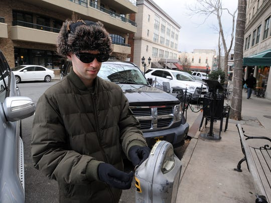 Matt Dalsanto of Agusta GA, feeds a parking meter while