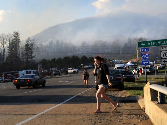 Local residents watch as a out-of-control wild fire consumes land near the Ridgecrest area near Black Mountain Tuesday afternoon March 31, 2015.