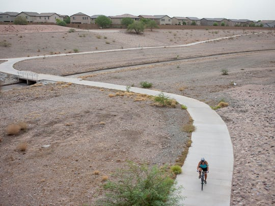 A biker rides on Skunk Creek trail near the 75th Ave bridge in Peoria. Glendale is recruiting volunteers to help pick up trash and debris along the New River and Skunk Creek trail systems on Saturday, April 18, 2015.