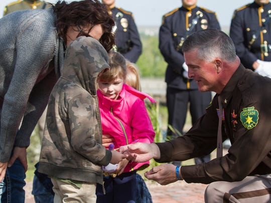 Cascade County Sheriff Bob Edwards hands out commemorative coins to Joey and Shiloh Dunn, the children of fallen officer Deputy Joe Dunn during Monday morning's dedication ceremony at the new Law Enforcement Memorial on Flag Hill.