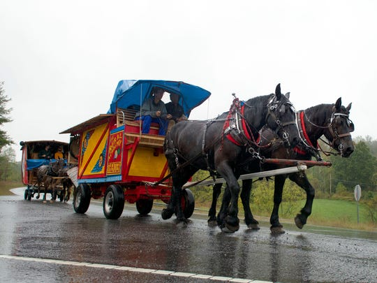 Driver Jais Brohinsky and Noah Harrell lead a team of horses in front of a second carriage driven by Eric Endres and Jeff Reinhardy in a caravan of carriages that make up the Rural Academy Theater group traveling from Mars Hill to Marshall along North Carolina Highway 213 Tuesday.