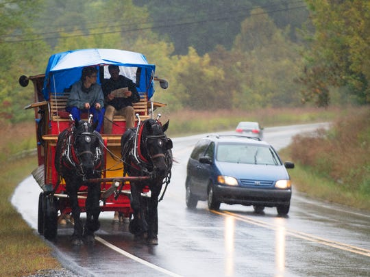 Driver Jais Brohinsky and Noah Harrell watch for traffic while leading a team of horses in front of a second carriage driven by Eric Endres and Jeff Reinhardy in a caravan of carriages that make up the Rural Academy Theater group traveling from Mars Hill to Marshall along North Carolina Highway 213 Tuesday.