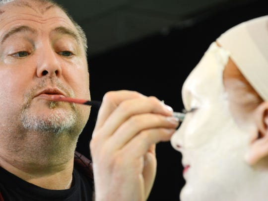 Alan Ostrander of AEO Studios applies makeup to Christina LaFortune Tuesday. He and Ray Asiala are designing the characters for this year's Trail of Terror at Brevard Zoo.