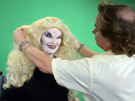 Ray Asiala  of AEO Studios helps Christina LaFortune with a wig Tuesday. Asiala and Alan Ostrander are designing the characters for this year's Trail of Terror at Brevard Zoo.